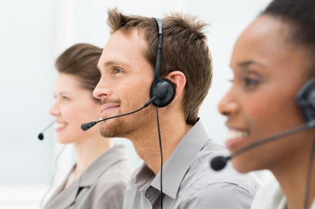 helpdesk: Closeup Of Happy Telephone Operators In A Row