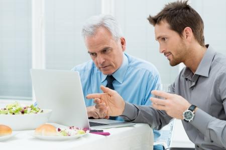 trabajando: Dos personas de negocios que trabajan en la computadora port�til en el almuerzo en restaurante