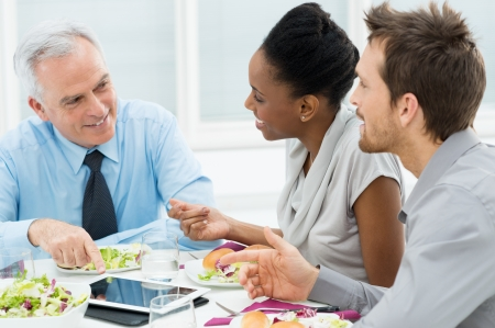 ethnic women: Business Colleagues Eating Meal Together While Discussing of Work Stock Photo