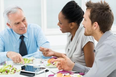lunchen: Zakelijke Collega's Eating Maaltijd samen Terwijl Bespreken van Werk Stockfoto