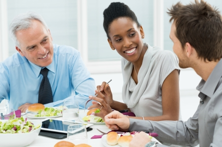 Business Colleagues Eating Meal Together and Discussing of Work Stock Photo