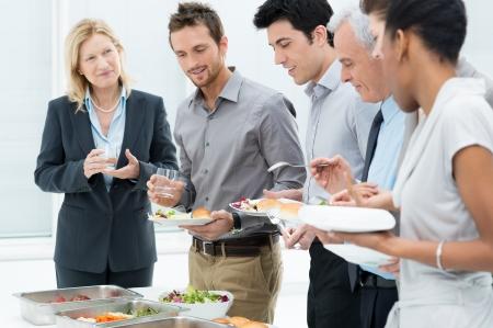 office break: Colegas del asunto que come la comida junto en restaurante Foto de archivo