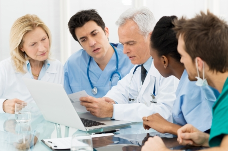 medical physician: Team Of Expert Doctors Examining Medical Reports at Hospital Stock Photo
