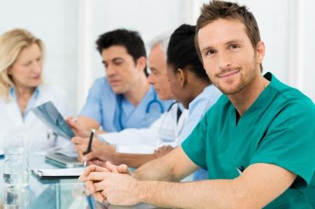 彼のチームと若い幸せな外科医の肖像画 写真素材
