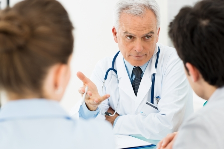 hombre preocupado: Doctor Maduro Participa en la discusi�n seria con sus pacientes Foto de archivo
