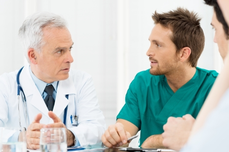 health professionals: Group Of Doctors Involved In Serious Discussion at Hospital Stock Photo