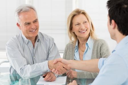 Senior Gelukkig Paar Schudden Hand Met Financieel Adviseur Stockfoto