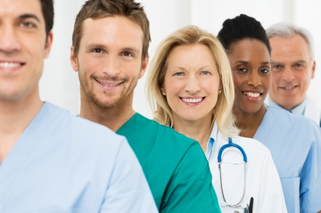 practitioner: Group Of Happy Successful Doctors Standing In A Row At Hospital Stock Photo