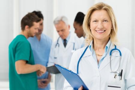 grupo de médicos: Feliz Doctora se coloca delante de su compañero de trabajo Foto de archivo