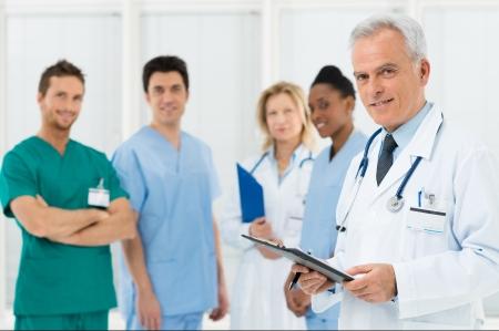 staff medico: Ritratto di un medico e dei suoi colleghi con le cartelle sanitarie