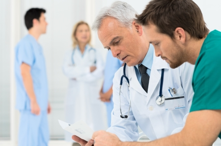 serious meeting: Group Of Doctors Involved In Serious Discussion With Medical Records Stock Photo