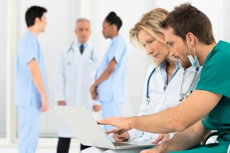 personal medico: Grupo de m�dicos que trabajan en la computadora port�til en el hospital Foto de archivo