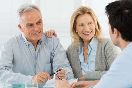 agents: Portrait Of Happy Senior Couple Talking With A Young Man