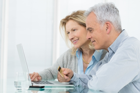 booking: Portrait Of Senior Couple Shopping Online With Credit Card