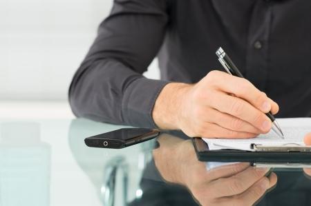 hombre escribiendo: Hombre de negocios que examina un contrato y la escritura en el papel