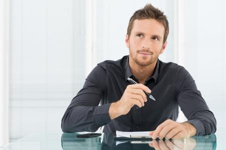 escribiendo: Hombre de negocios joven que piensa y pregunta al escribir un papel