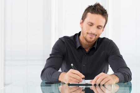 lectura y escritura: Retrato del hombre de negocios Escribir un papeleo en la oficina Foto de archivo