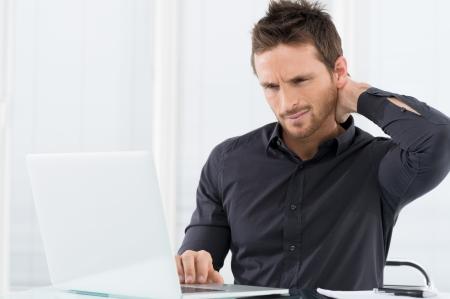dolor de espalda: Empresario cansado trabajar en la computadora port�til Foto de archivo