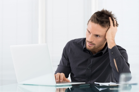 worried executive: Stressed Man Working On Laptop Stock Photo