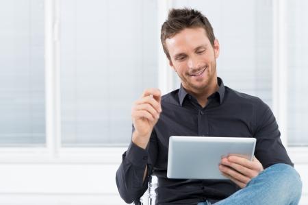 empresario: Retrato de un joven apuesto hombre feliz que usa la tableta digital Foto de archivo