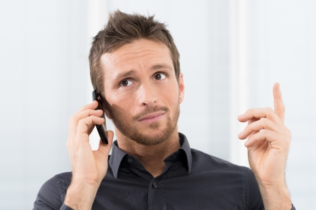 seriously: Businessman Listening Seriously On Mobile Phone In Office Stock Photo