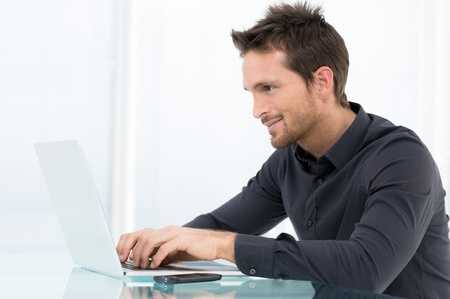 Happy Businessman Working On Laptop In Office