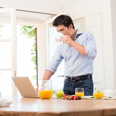 dejeuner: Portrait de jeune homme Utiliser un ordinateur portable pendant le petit-
