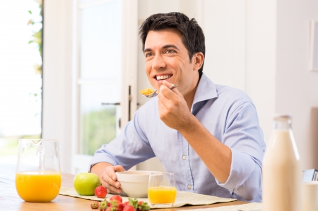 crunchy: Happy Young Man Having Healthy Breakfast Stock Photo