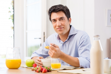 cereal: Portrait Of Happy Young Man Having Healthy Breakfast