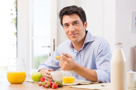 eating breakfast: Portrait Of Happy Young Man Having Healthy Breakfast