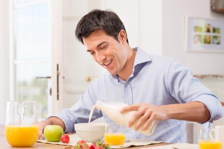 幸せな青年が牛乳を注いでボウルに朝食のため