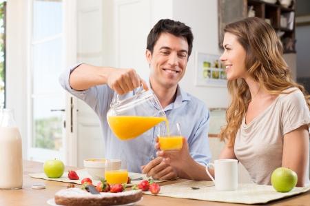saludable: Retrato de hombre feliz Verter el jugo en vidrio para la mujer joven