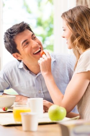 Happy Young Woman Feeding Strawberry To Man photo