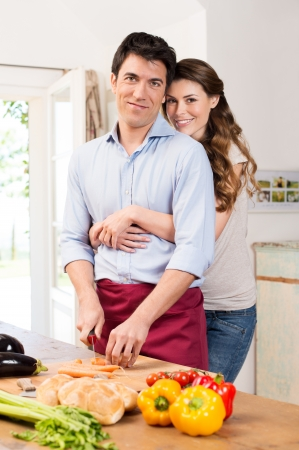 Young Woman Embracing Man Working In Kitchen photo