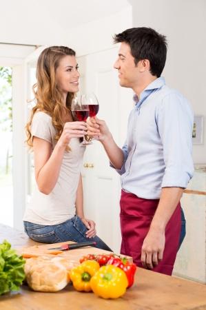 romântico: Jovem casal feliz que cozinha na cozinha Imagens