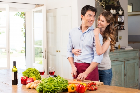 cutting vegetables: Young Beautiful Woman Embracing Man Working In Kitchen