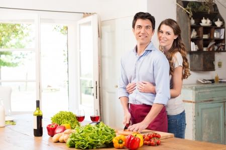 cuchillo de cocina: Mujer hermosa joven abrazando al hombre de trabajo en la cocina