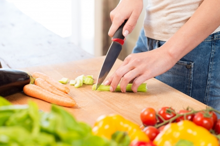 Close-up Of Girls Hand Cutting Celery On Chopping Board photo