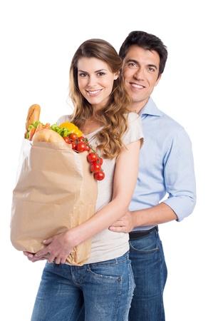 Retrato de la feliz pareja joven con la bolsa de comestibles aislados en fondo blanco