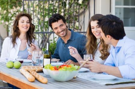 hombre comiendo: Grupo de amigos felices que cenan en Patio