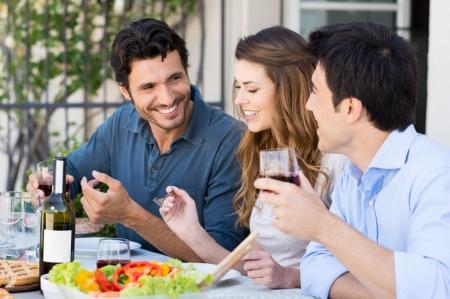 屋外のパティオで食事をして幸せな友人のグループ 写真素材