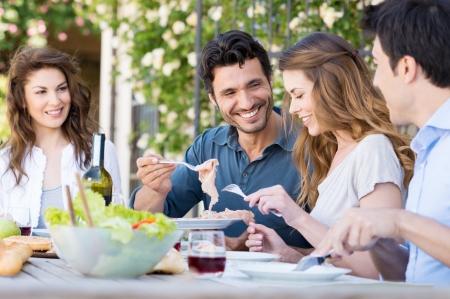 comiendo pan: Grupo de amigos felices j�venes que cenan en Patio