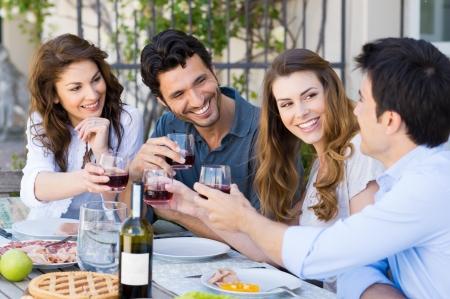 Gruppo di giovani amici felici che tostano vino di vetro esterna pur avendo il pranzo Archivio Fotografico - 20837981