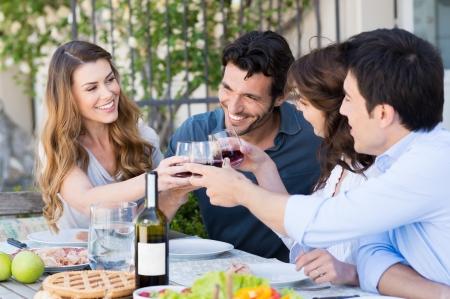 outdoor: Feliz jóvenes amigos Comer juntos al aire libre