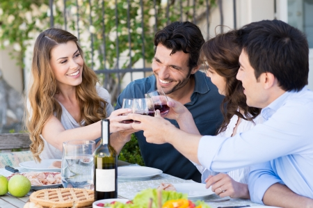 lifestyle dining: Happy Young Friends Eating Together Outdoor Stock Photo