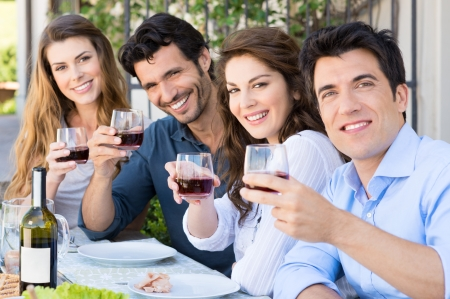 Drinking wine: Portrait Of Happy Young Group Friends Holding Wine Glass Outdoor
