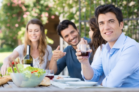 latinos: Young Man Holding Glass Of Wine With His Friends In Background