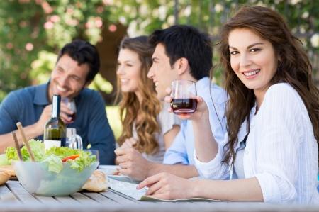 jovenes tomando alcohol: Feliz mujer con vaso de vino con sus amigos en el fondo