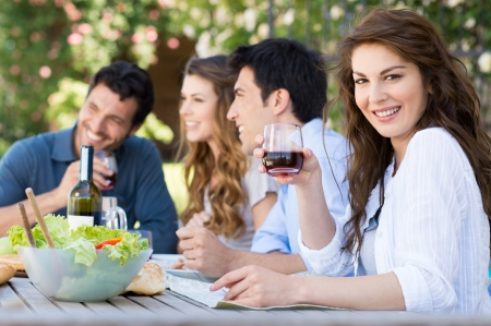 wine and food: Happy Woman Holding Glass Of Wine With His Friends In Background