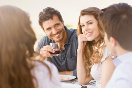 屋外ディナーを楽しんで幸せな若いお友達のグループ